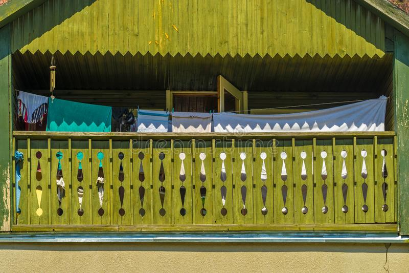 El verde pintó el balcón de madera de la casa con el lavadero en un día de verano caliente soleado imagen de archivo libre de regalías