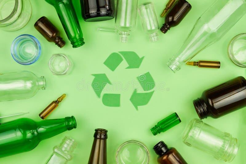 El verde recicla símbolo de la muestra con la basura de cristal de la basura imagen de archivo libre de regalías