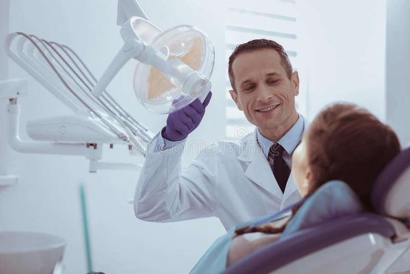 El verificar masculino alegre del dentista oral limpia foto de archivo libre de regalías