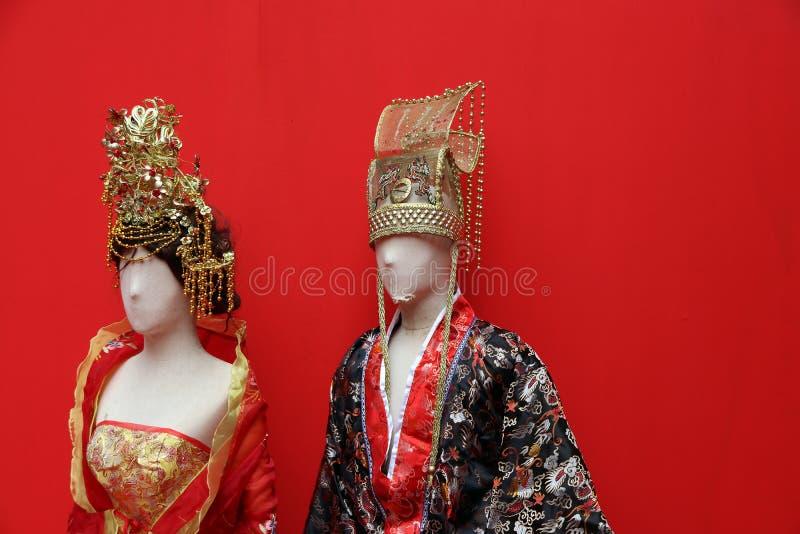 El vestido chino de la tradición del varón y de la hembra se vista en maniquí con el fondo rojo foto de archivo