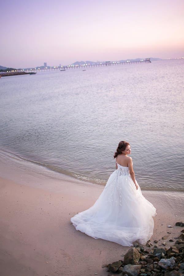 El vestido de boda joven atractivo del desgaste de la novia y el velo blanco, se colocan solamente en la playa del mar foto de archivo