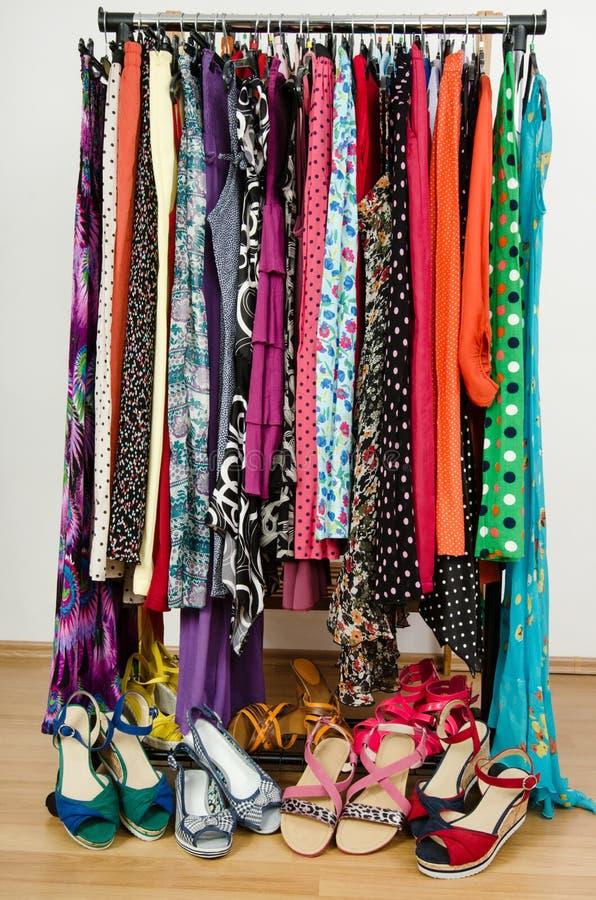 el vestido del armario con ropa y zapatos coloridos arregl agradable en un estante
