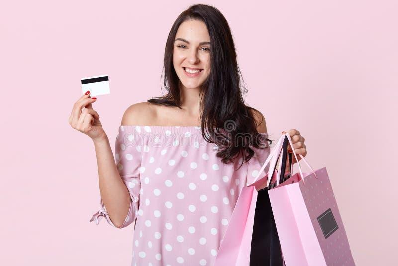 El vestido elegante hermoso del lunar de la mujer que lleva joven, sosteniendo bolsos de compras y la tarjeta de crédito, se colo imagen de archivo