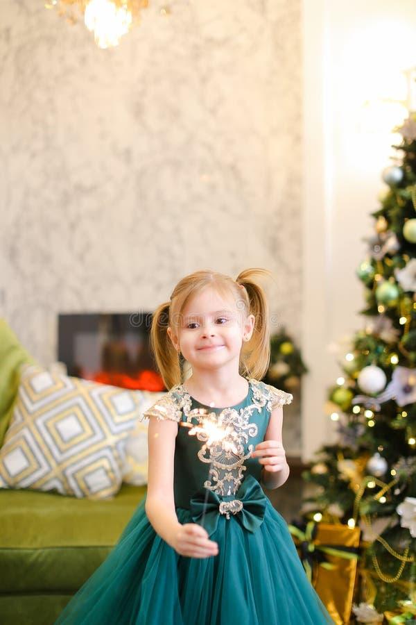 El vestido que lleva y la situación de la pequeña muchacha linda con las luces de Bengala acercan al árbol de navidad fotografía de archivo