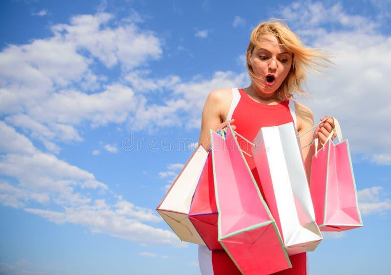 El vestido rojo de la mujer lleva el fondo del cielo azul de los panieres del manojo Muchacha satisfecha con las compras Mejor ma fotografía de archivo