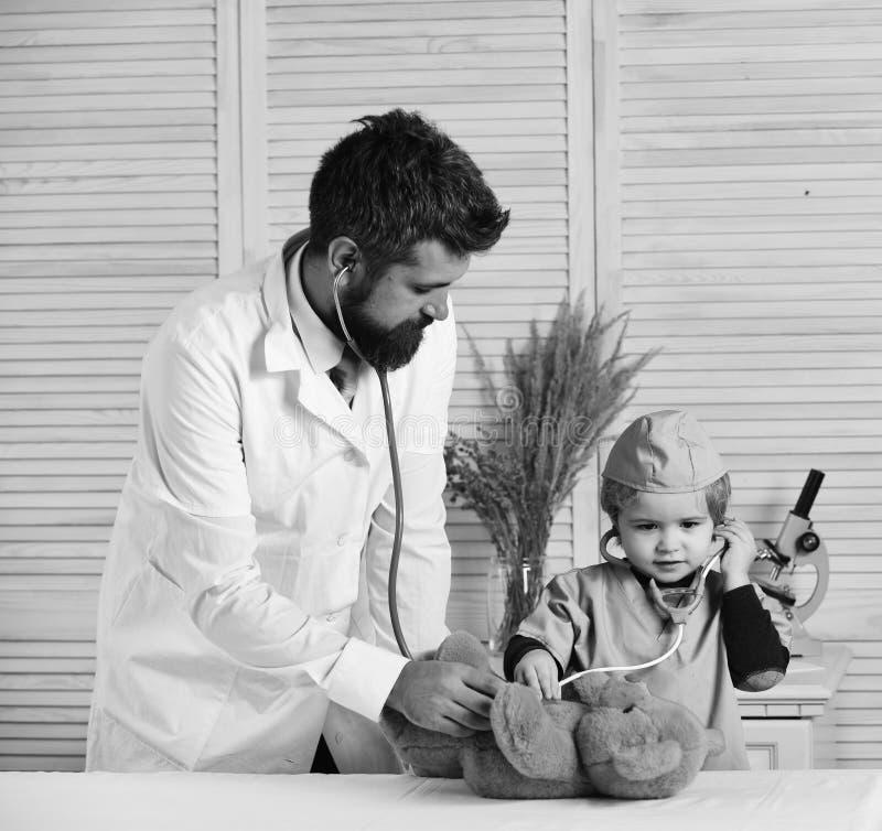 El veterinario y el pequeño ayudante examinan el oso de peluche Padre y niño con las caras atentas que juegan al doctor imagen de archivo libre de regalías
