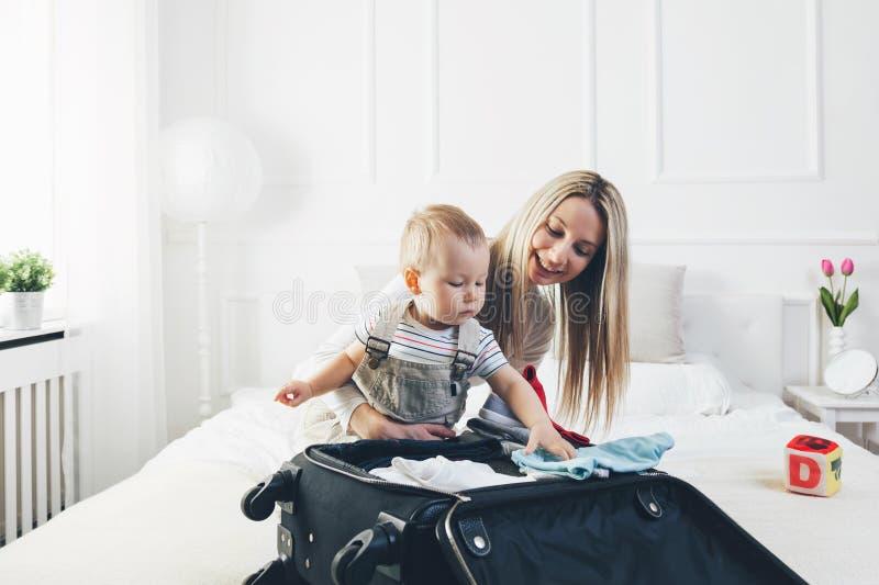 El viajar con los niños La madre feliz con su embalaje del niño viste para el día de fiesta fotografía de archivo libre de regalías