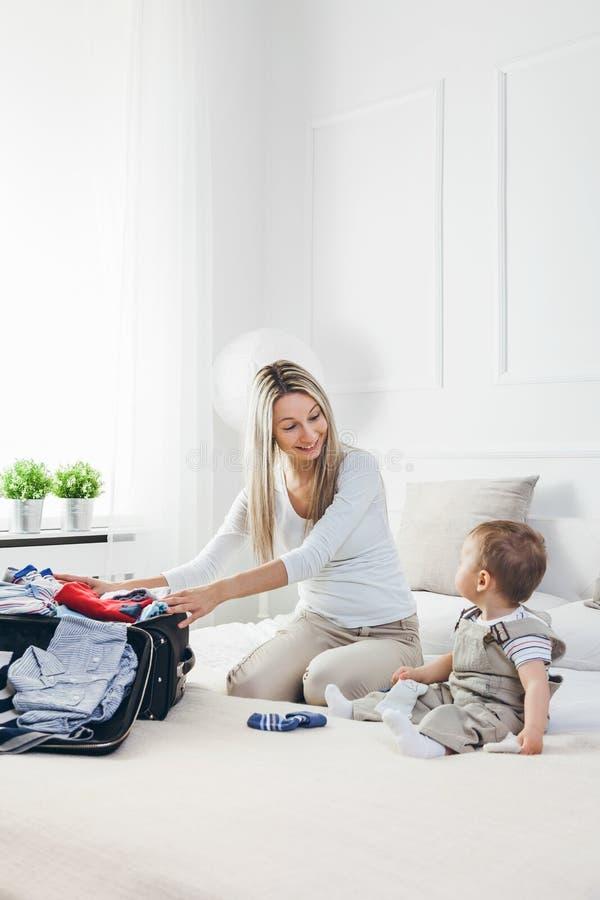 El viajar con los niños La madre feliz con su embalaje del niño viste para el día de fiesta imágenes de archivo libres de regalías