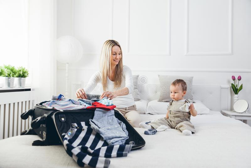 El viajar con los niños La madre feliz con su embalaje del niño viste para el día de fiesta foto de archivo libre de regalías