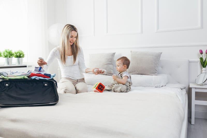 El viajar con los niños La madre feliz con su embalaje del niño viste para el día de fiesta foto de archivo