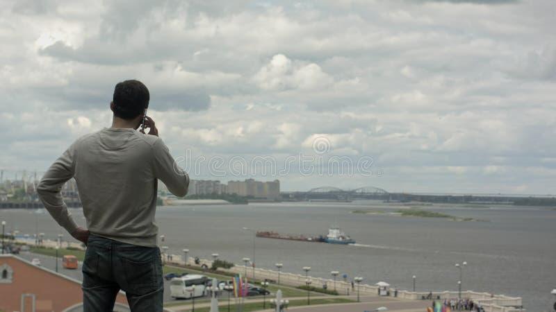 El viajar del hombre de negocios El hablar en su teléfono móvil cerca del río imágenes de archivo libres de regalías