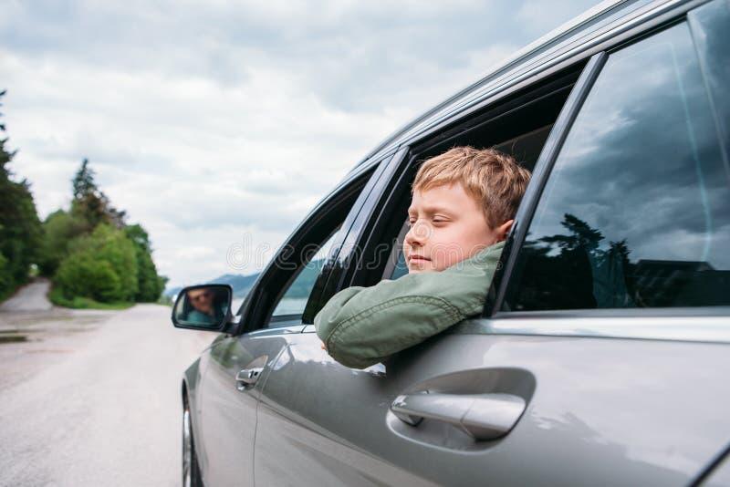 El viajar en auto - el hijo y el padre miran hacia fuera de las ventanillas del coche foto de archivo libre de regalías