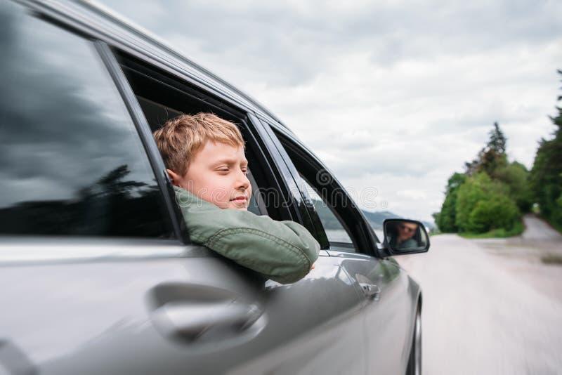 El viajar en auto - el hijo y el padre miran hacia fuera de las ventanillas del coche fotografía de archivo libre de regalías
