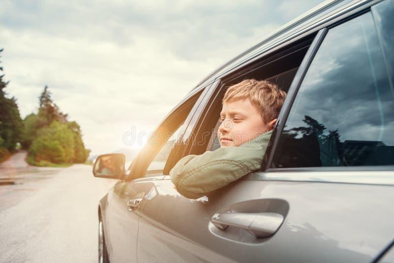 El viajar en auto - el hijo y el padre miran hacia fuera de las ventanillas del coche imagenes de archivo