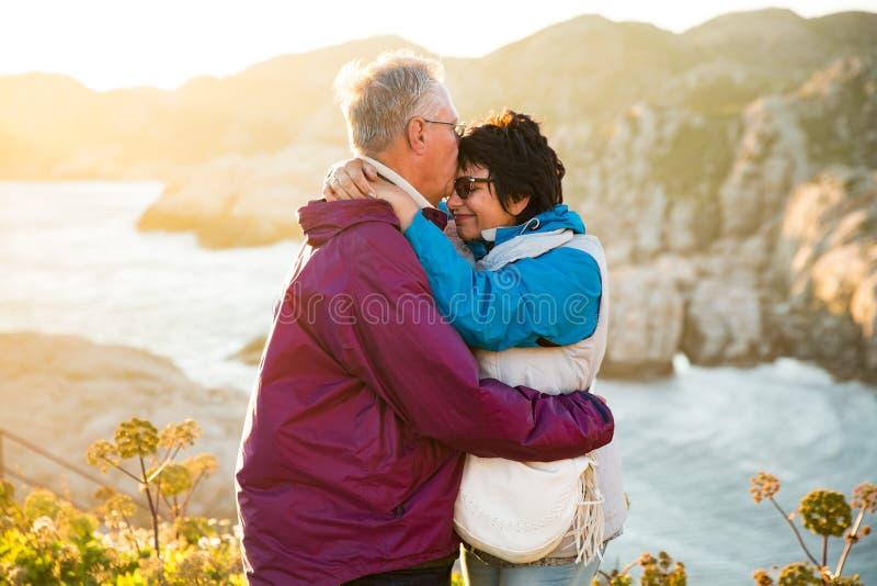 El viajar maduro cariñoso de los pares, colocándose en el top de la roca, explorando foto de archivo