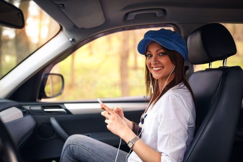 El viajar por la mujer automotriz que goza en el viaje por carretera que escucha imagen de archivo