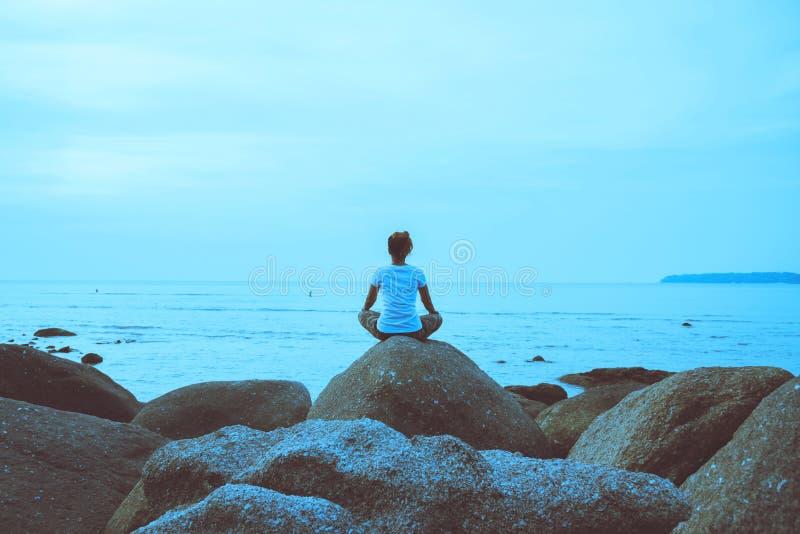 El viaje asi?tico de la mujer se relaja en el d?a de fiesta Juego si yoga En las rocas por el mar imágenes de archivo libres de regalías