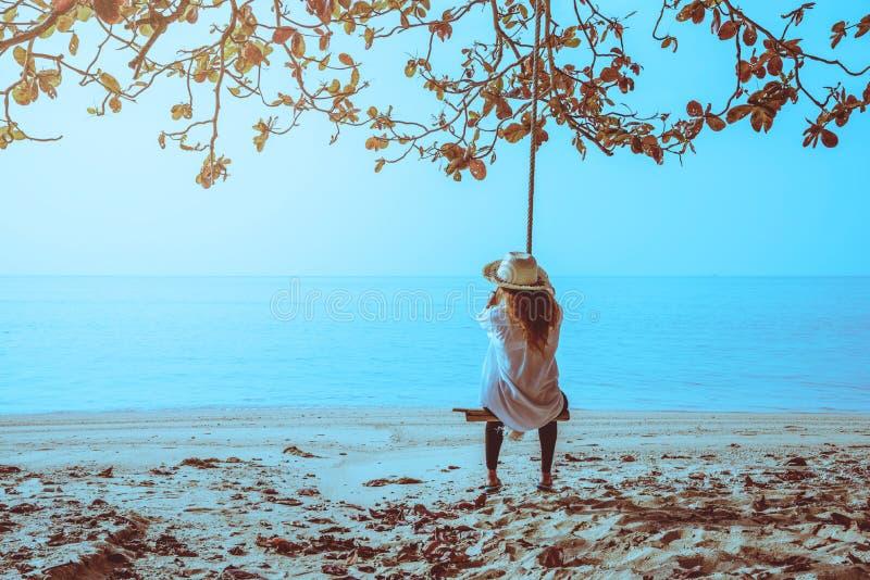 El viaje asi?tico de la mujer se relaja en el d?a de fiesta Si?ntese en un oscilaci?n en la playa imagen de archivo