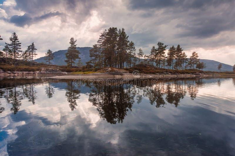 El viaje en la manera a la piedra del kjerag en las montañas kjeragbolten de Noruega, reflexión de árboles en el lago en los sole imagen de archivo libre de regalías