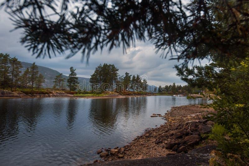 El viaje en la manera a la piedra del kjerag en las montañas kjeragbolten de Noruega, reflexión de árboles en el lago en los sole imágenes de archivo libres de regalías