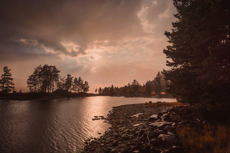 El viaje en la manera a la piedra del kjerag en las montañas kjeragbolten de Noruega, reflexión de árboles en el lago en los sole foto de archivo