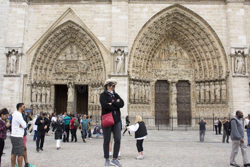 El viaje tailandés asiático de la mujer y la presentación para toman la foto en el Notre-Dame de Paris de Cathedrale fotografía de archivo