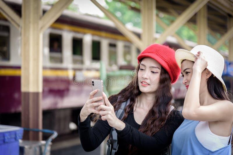 El viajero asiático de las mujeres tiene jugar un teléfono móvil y hablar para foto de archivo libre de regalías