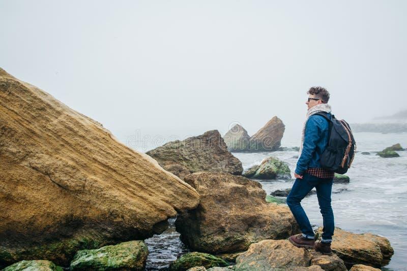 El viajero con una mochila se opone en una roca a un mar hermoso con las ondas, muchacho elegante del inconformista que presenta  fotografía de archivo libre de regalías