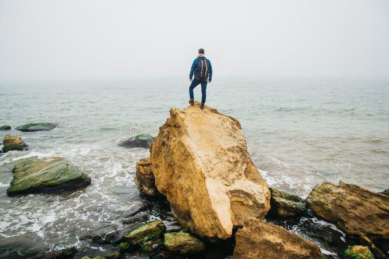 El viajero con una mochila se opone en una roca a un mar hermoso con las ondas, muchacho elegante del inconformista que presenta  imagen de archivo libre de regalías