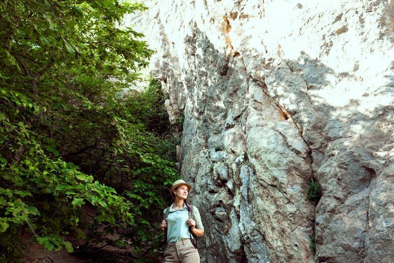 El viajero de la muchacha camina a través de las montañas y del bosque Él sonríe Pantalones cortos y moreno verdes de la camisa S imagenes de archivo