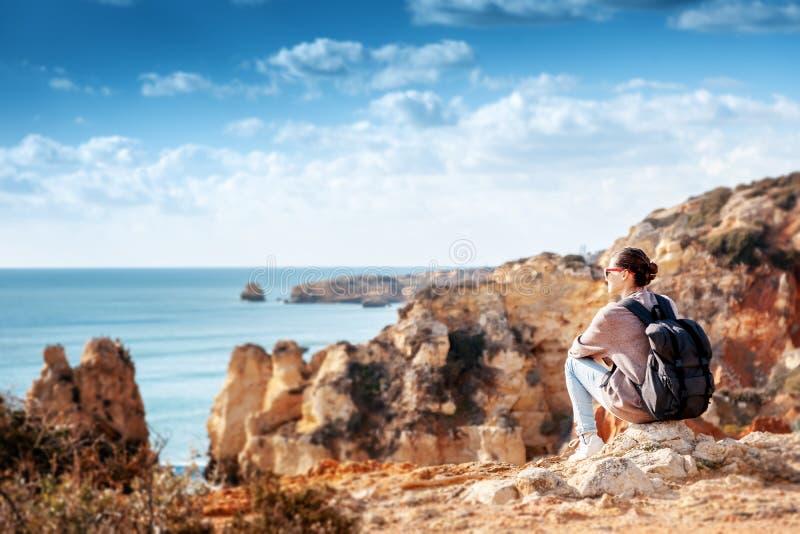 El viajero de la muchacha con una mochila se sienta en las rocas en el océano, anuncio foto de archivo libre de regalías