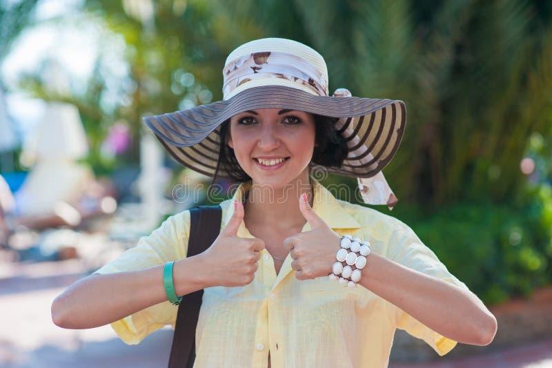 El viajero de la muchacha muestra bien Muchacha de reclinación con el sombrero y la camisa amarilla de los hombres foto de archivo libre de regalías