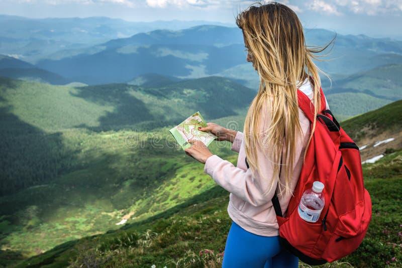 El viajero de la mujer mira el mapa en el Himalaya de las montañas, isla de Honshu, Kilimanjaro, Karakoram, montañas, Patagonia imagenes de archivo