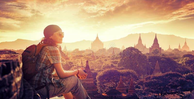 El viajero de la mujer se sienta en puesta del sol y disfruta de la visión fotografía de archivo