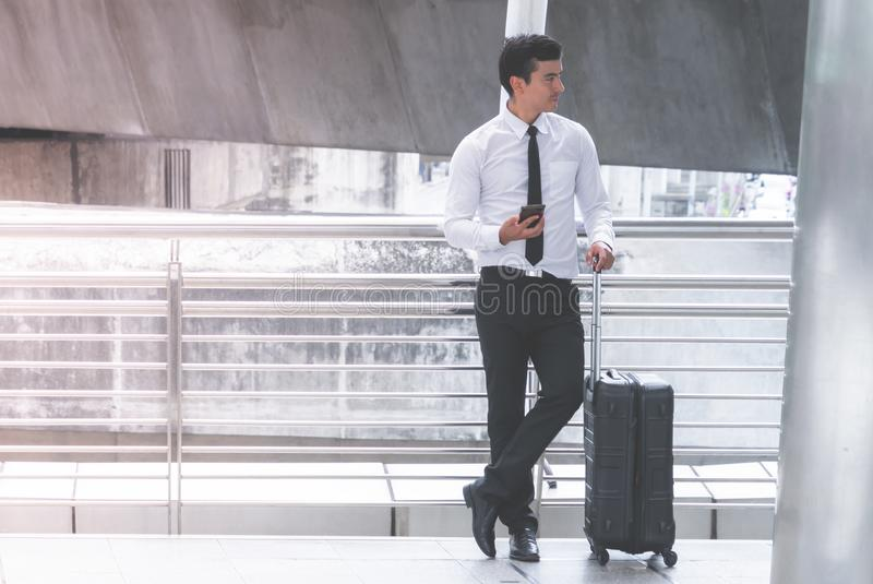 El viajero de negocios con equipaje está utilizando su teléfono móvil fotografía de archivo