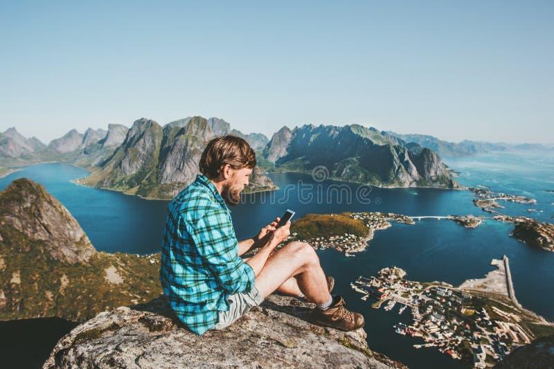 El viajero del hombre que usa el smartphone que se sienta en las montañas remata fotos de archivo libres de regalías