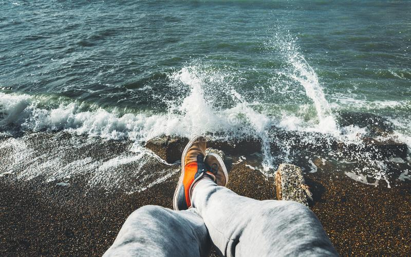 El viajero del hombre se sienta en el viaje de Cliff Overlooking The Sea Surf, tiro de Point of View Concepto de las vacaciones d fotografía de archivo