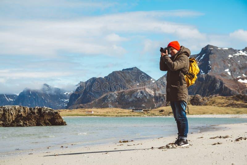 El viajero es fotógrafo profesional que asume el control el paisaje de la foto del paisaje Llevar una mochila amarilla en un rojo foto de archivo