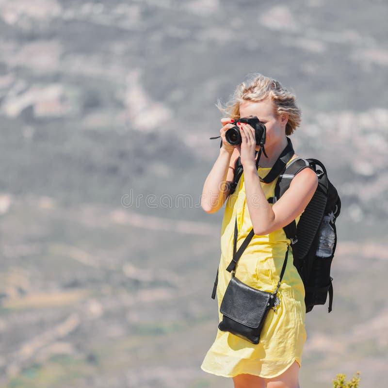 El viajero femenino con una mochila en ella detrás que disfruta de las visiones desde las montañas de Montserrat en España y hace imagen de archivo libre de regalías