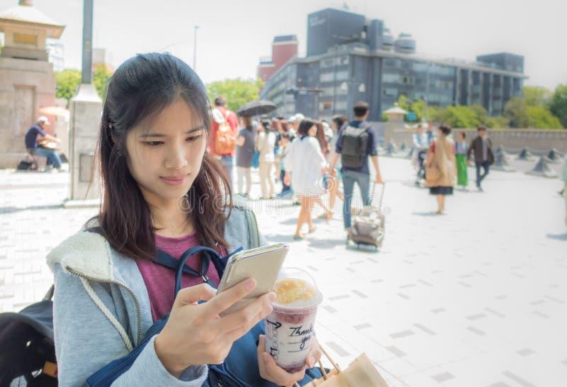 El viajero femenino está utilizando el teléfono en Harajuku imagen de archivo