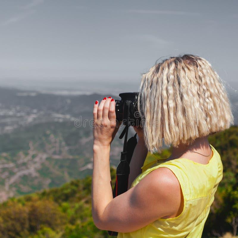 El viajero femenino que disfruta de las visiones desde las montañas de Montserrat en España y hace una foto imagen de archivo
