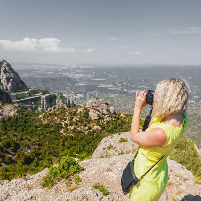 El viajero femenino que disfruta de las visiones desde las montañas de Montserrat en España y hace una foto imágenes de archivo libres de regalías