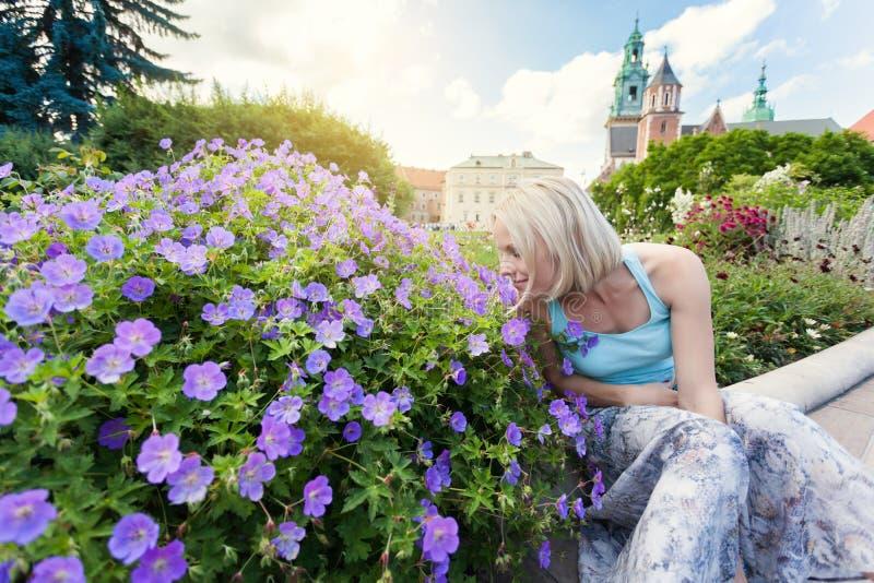 El viajero femenino que se sienta y las flores el oler en el fondo de Wawel se escuda foto de archivo