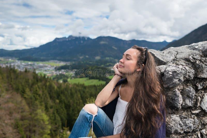 El viajero femenino se sienta en el pico de la montaña imágenes de archivo libres de regalías