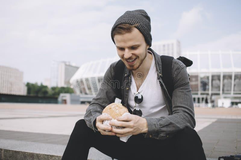 El viajero hambriento se está sentando en los pasos en la calle no muy lejos de estadio grande imagen de archivo