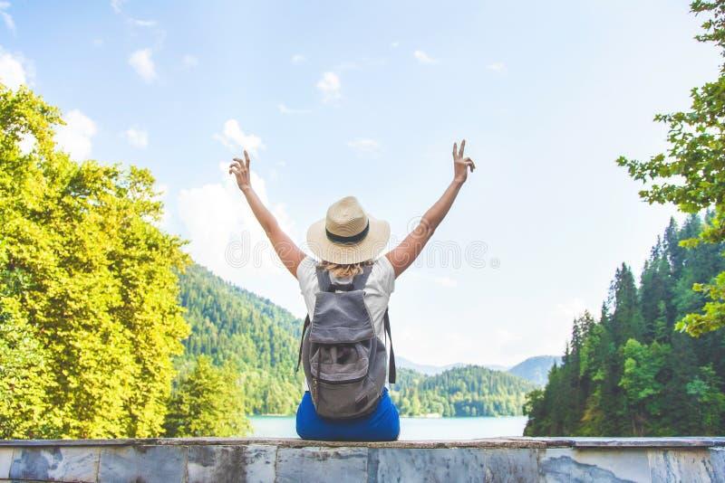 El viajero hermoso de la muchacha se sienta en un lago azul grande de la montaña en un fondo de montañas que ella agita sus manos foto de archivo