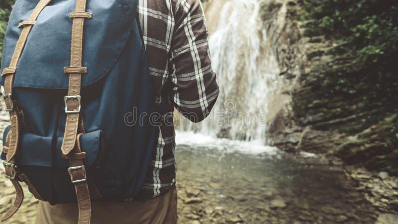 El viajero irreconocible con la mochila alcanzó el suyo y soportes en el primer del fondo de la cascada que caminaba concepto del foto de archivo