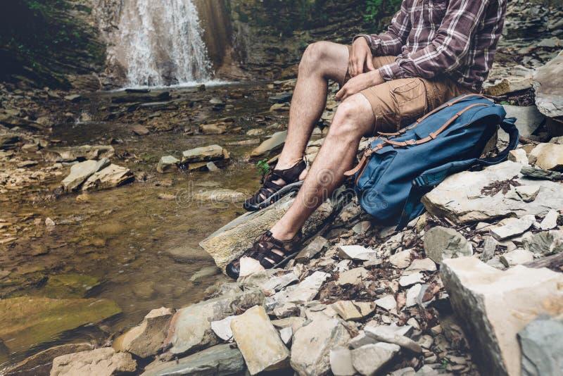 El viajero irreconocible con la mochila se sienta en el río y disfruta de la aventura de exploración de la visión circundante que fotografía de archivo