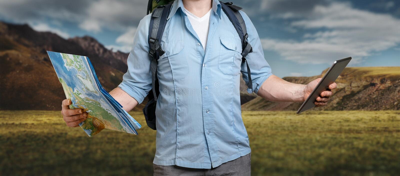 El viajero joven con una mochila sostiene el mapa y la tableta de papel T imagenes de archivo