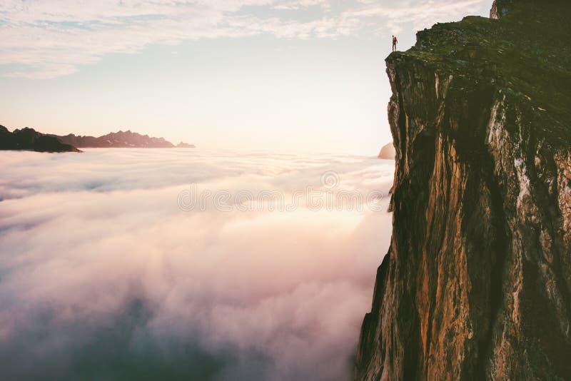 El viajero que se coloca en el top de la montaña del borde del acantilado sobre puesta del sol se nubla imágenes de archivo libres de regalías